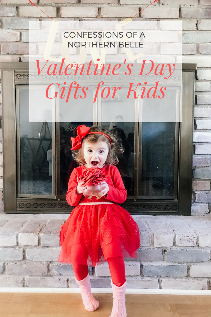 Little girl wearing red bow and red dress holding red rose pretending to take a bite and smiling - Valentine's Day Gifts for Kids