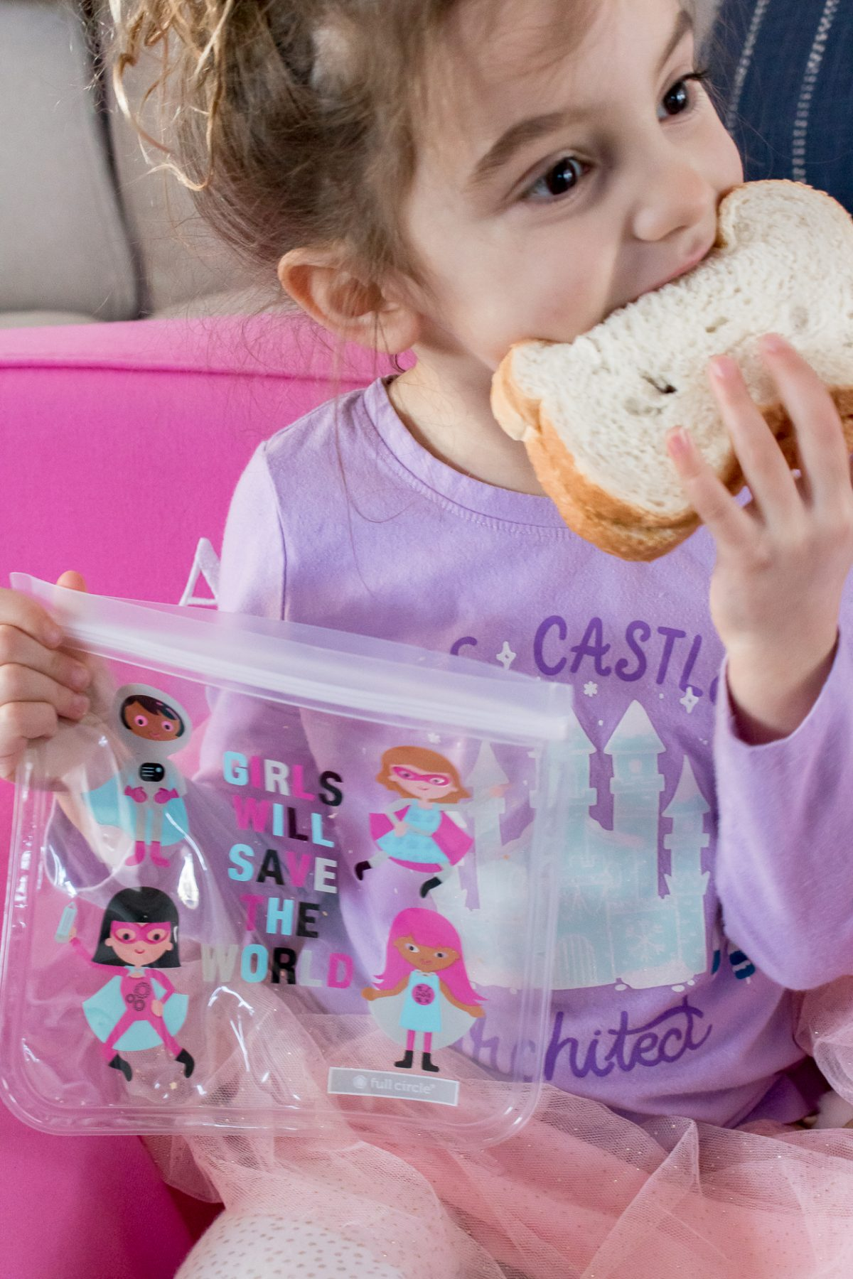 Little girl wearing a purple shirt holding reusable snack bag with sandwich inside that says Girls Will Save the World