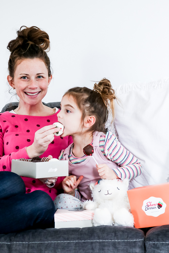 Woman in pink polka dot shirt feeding chocolate covered strawberry to little girl wearing pink and blue striped shirt