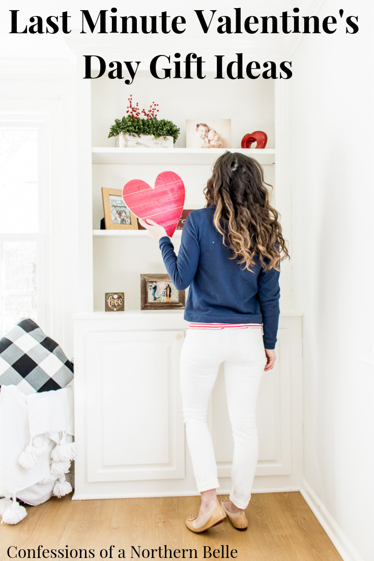 Woman wearing blue shirt holding a red heart and looking at a shelf - Last Minute Valentine's Day Gifts