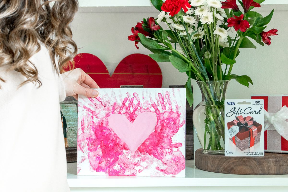 Woman holding a Pink Handprints and Pink Heart on a Canvas on a shelf
