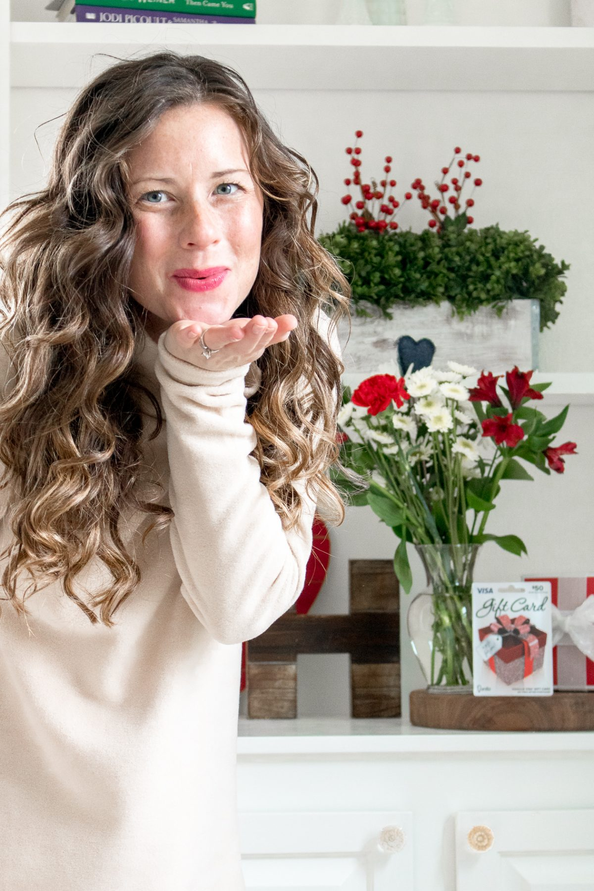 Woman wearing tan shirt and pink lipstick blowing a kiss at the camera - Last Minute Valentine's Day Gifts