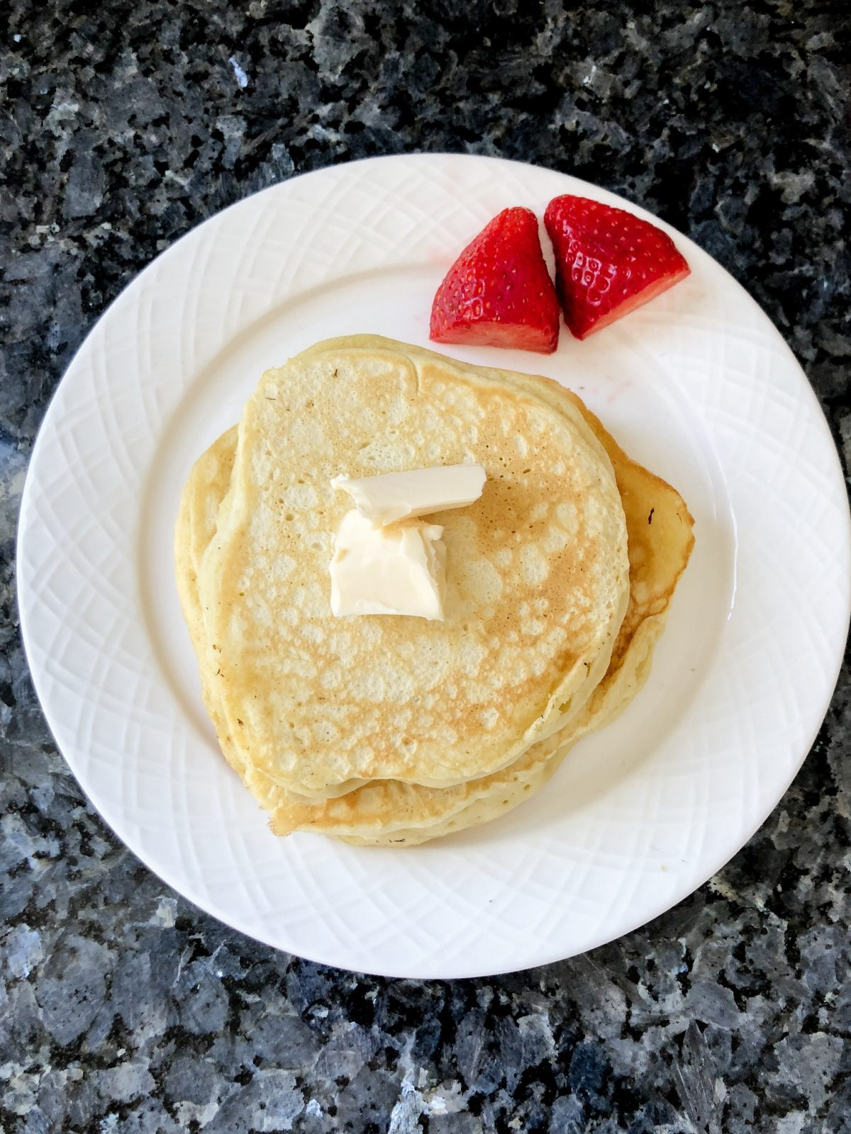 Pancakes with butter on top and two strawberries on a white plate