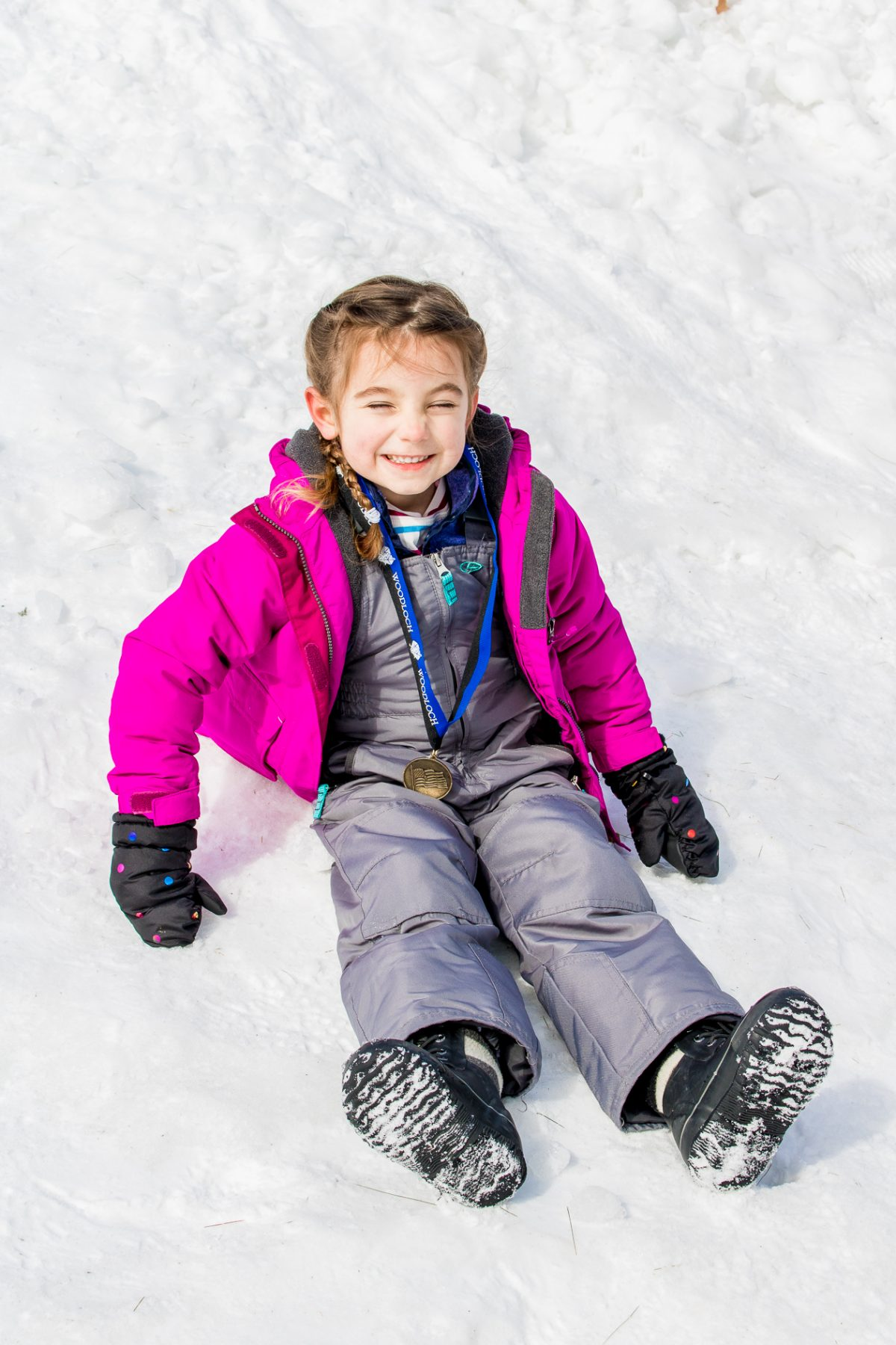 Little girl wearing snow suit and medal sitting in snow at Woodloch Pines Resort in Pocono Mountains