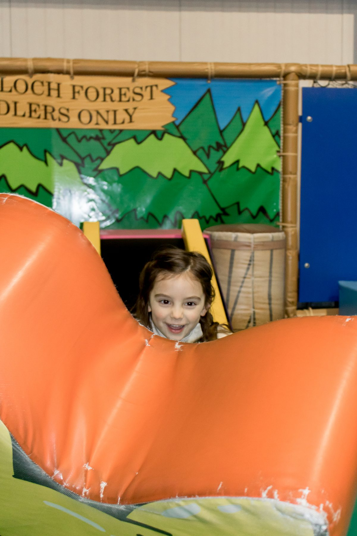Little girl wearing tan sweater and smiling while playing at Woodloch Forest Toddlers Only Play Area