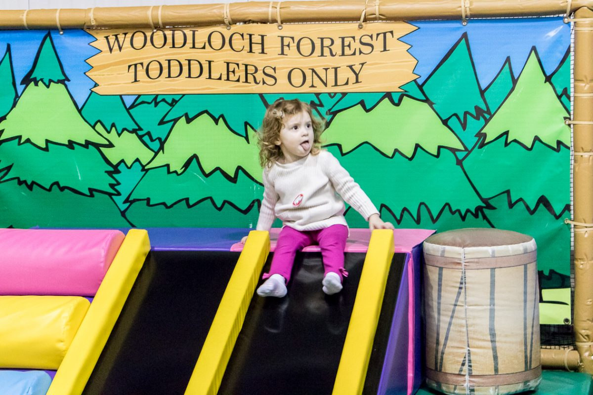 Little girl wearing tan sweater and pink leggings sticking out tongue while sitting on a slide at Woodloch Forest Toddlers Only Play Area