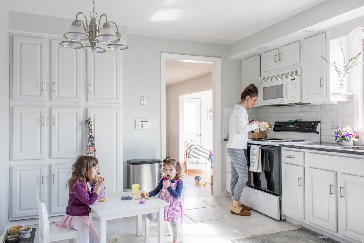 Woman using Bon Ami Powder Cleanser to clean stovetop while kids sit and eat lunch at table in kitchen