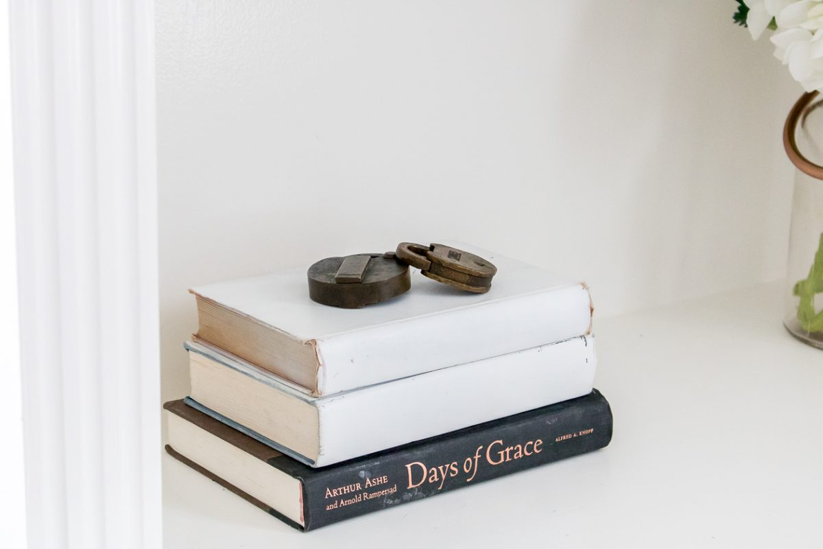 Two White books stacked on top of black book with antique locks on top