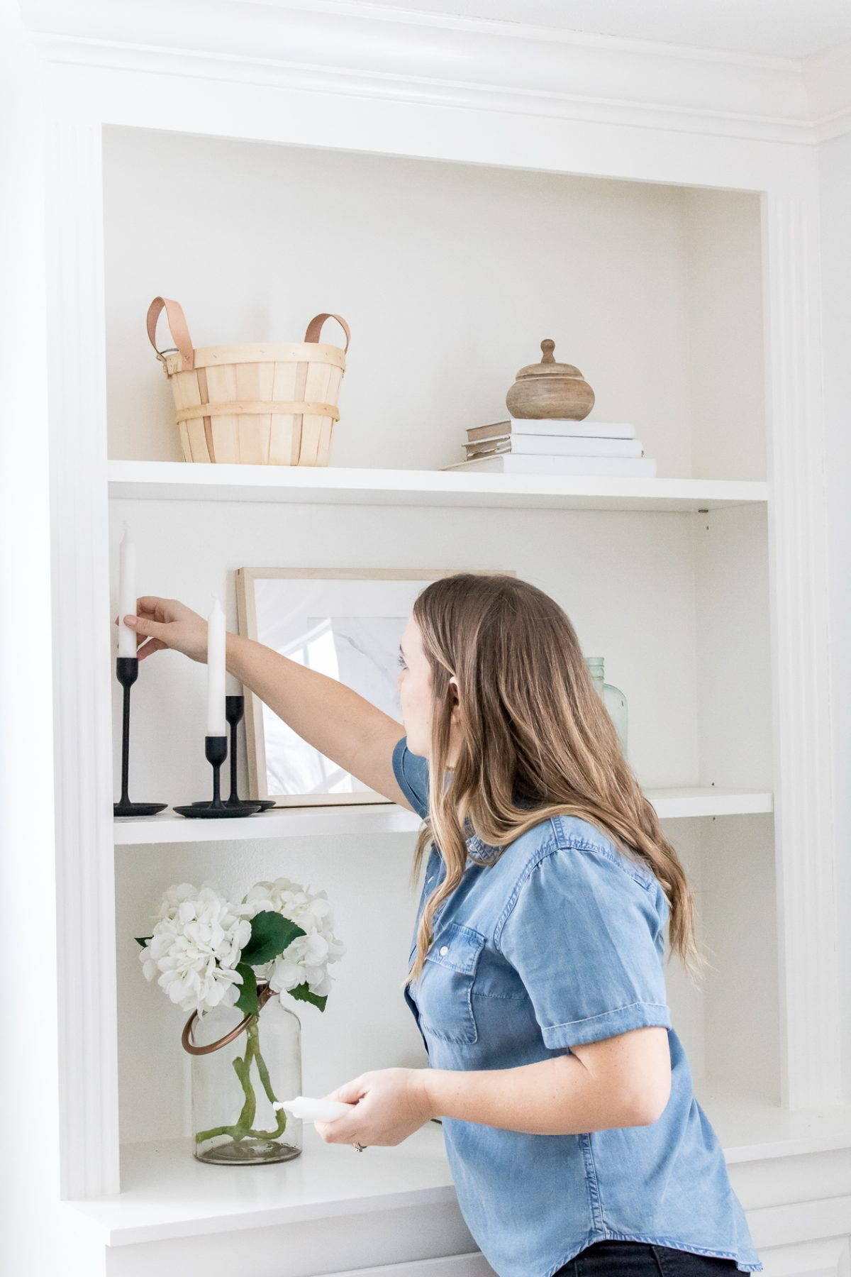 Woman in chambray shirt decorating built in shelves with black candle stick holders