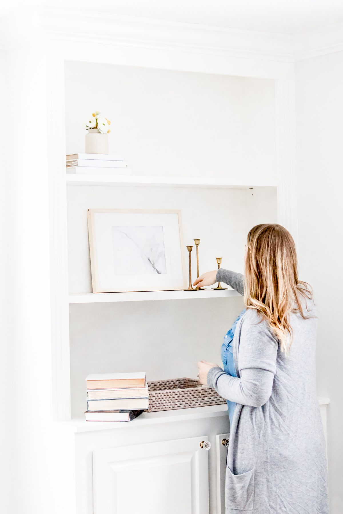 Woman wearing gray sweater and placing candlesticks on white shelf