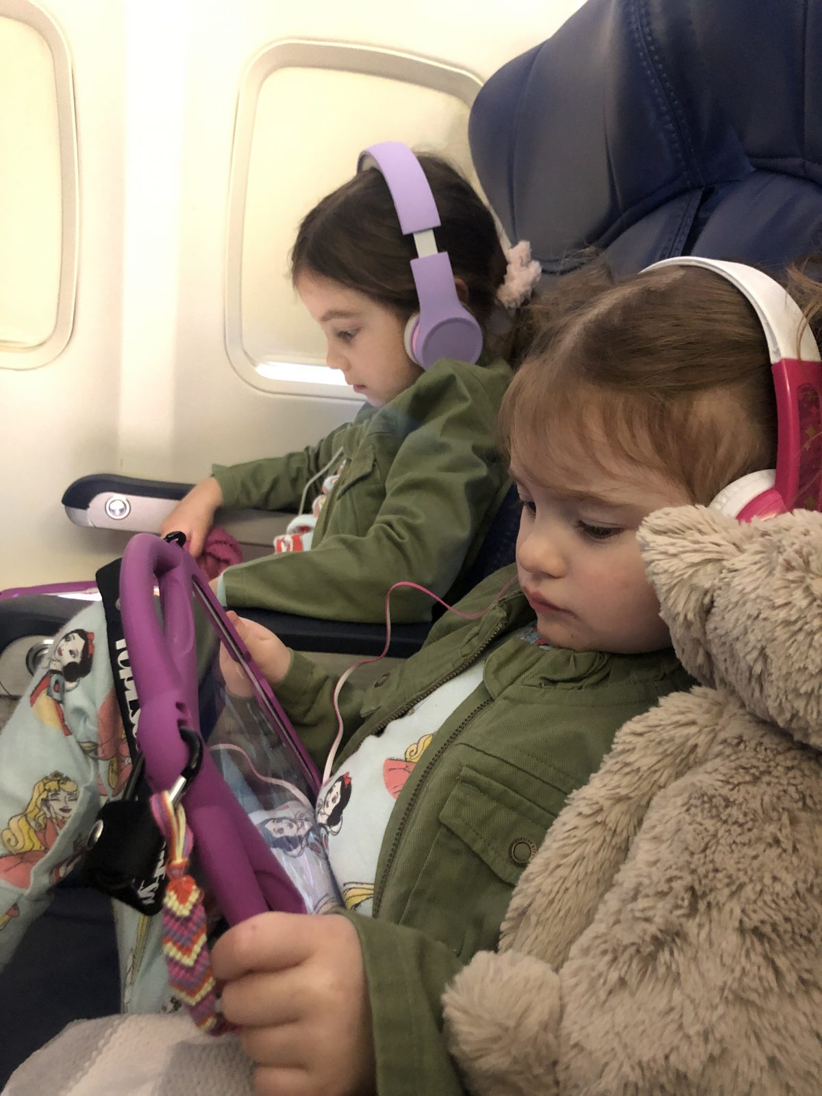 Toddlers wearing headphones and watching ipads on a plane