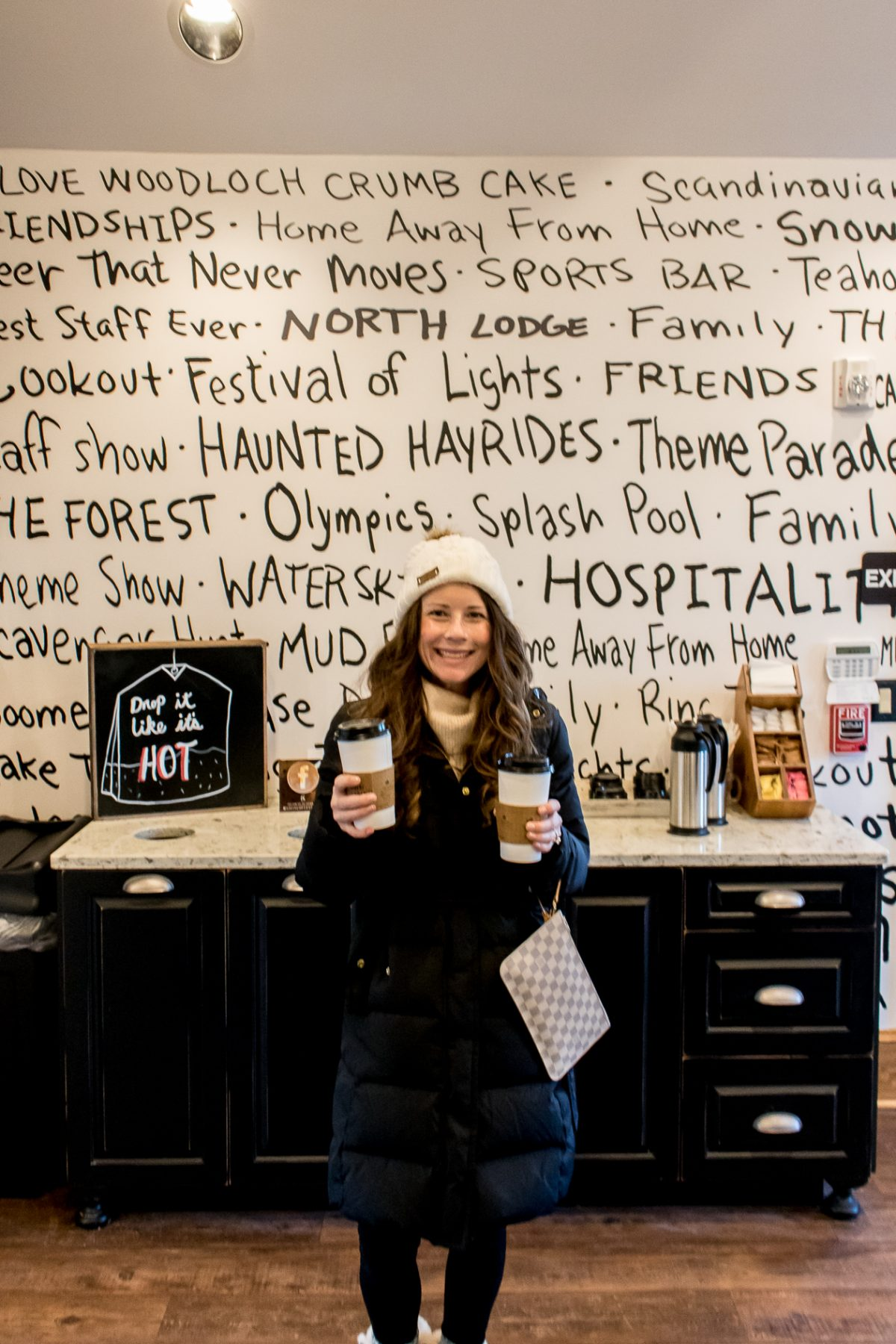 Woman holding two coffees at Gigi's Coffee House Woodloch Pines Pocono Mountains