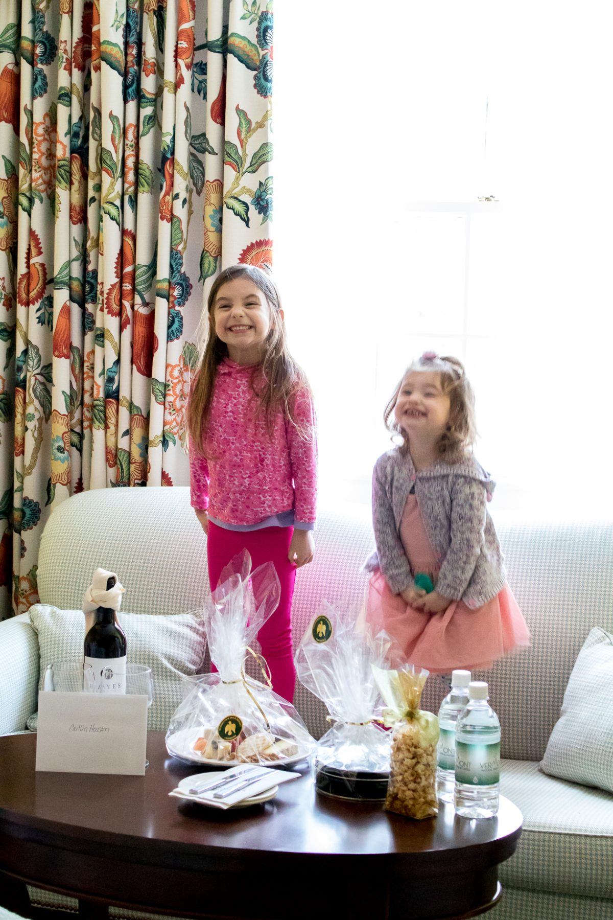 Smiling little girls wearing pink standing around a table with gifts Woodstock Inn and Resort in Woodstock Vermont