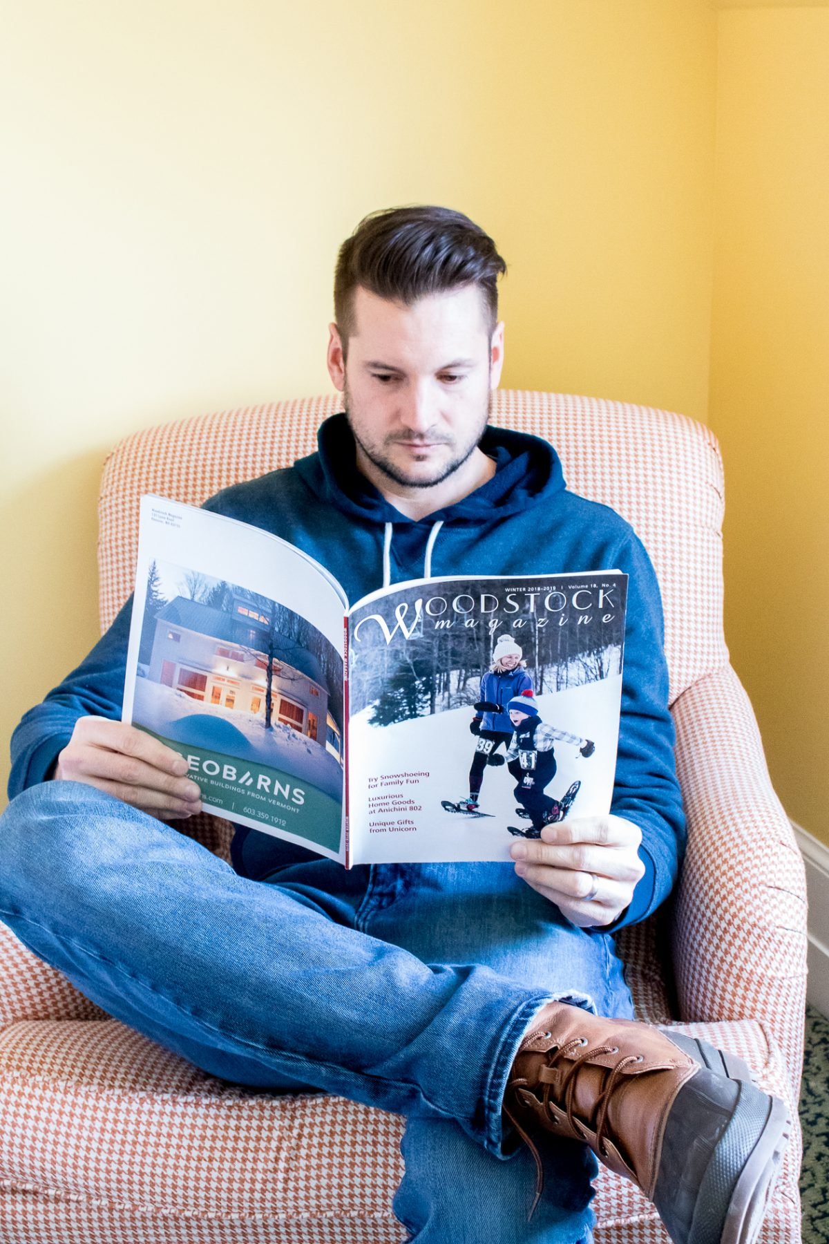 Man wearing a blue sweatshirt reading a Woodstock magazine in a pink chair at Woodstock Inn and Resort in Woodstock Vermont