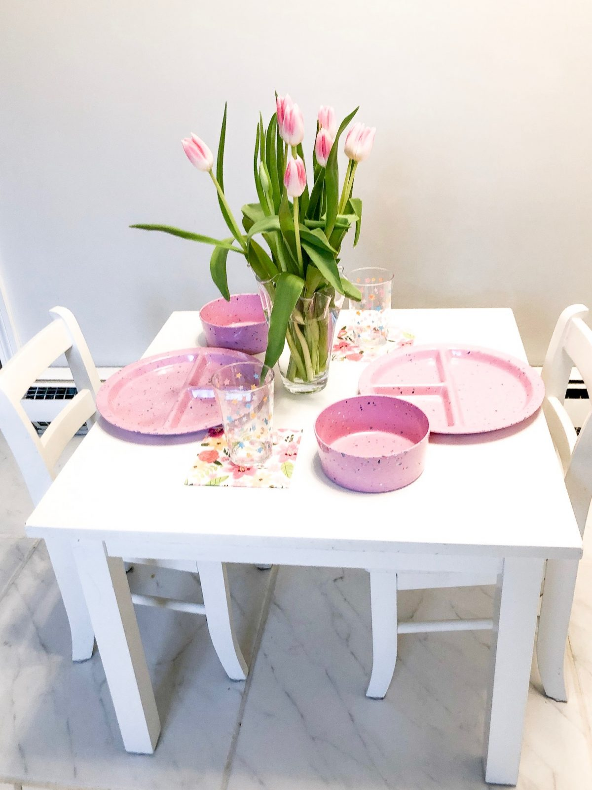 pink tulips and pink toddler plates, cups, and bowls on white toddler table