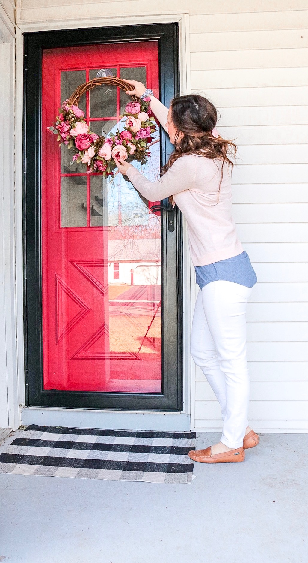 woman in pink sweater and light blue shirt with white pants hanging a pink floral wreath on a storm door outside