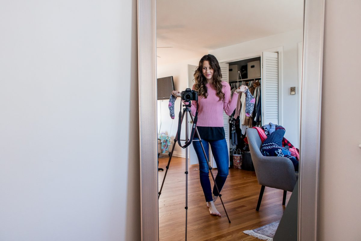 Woman in pink sweater and jeans holding a dirty sock standing at her camera taking a photo of the reflection of her messy room