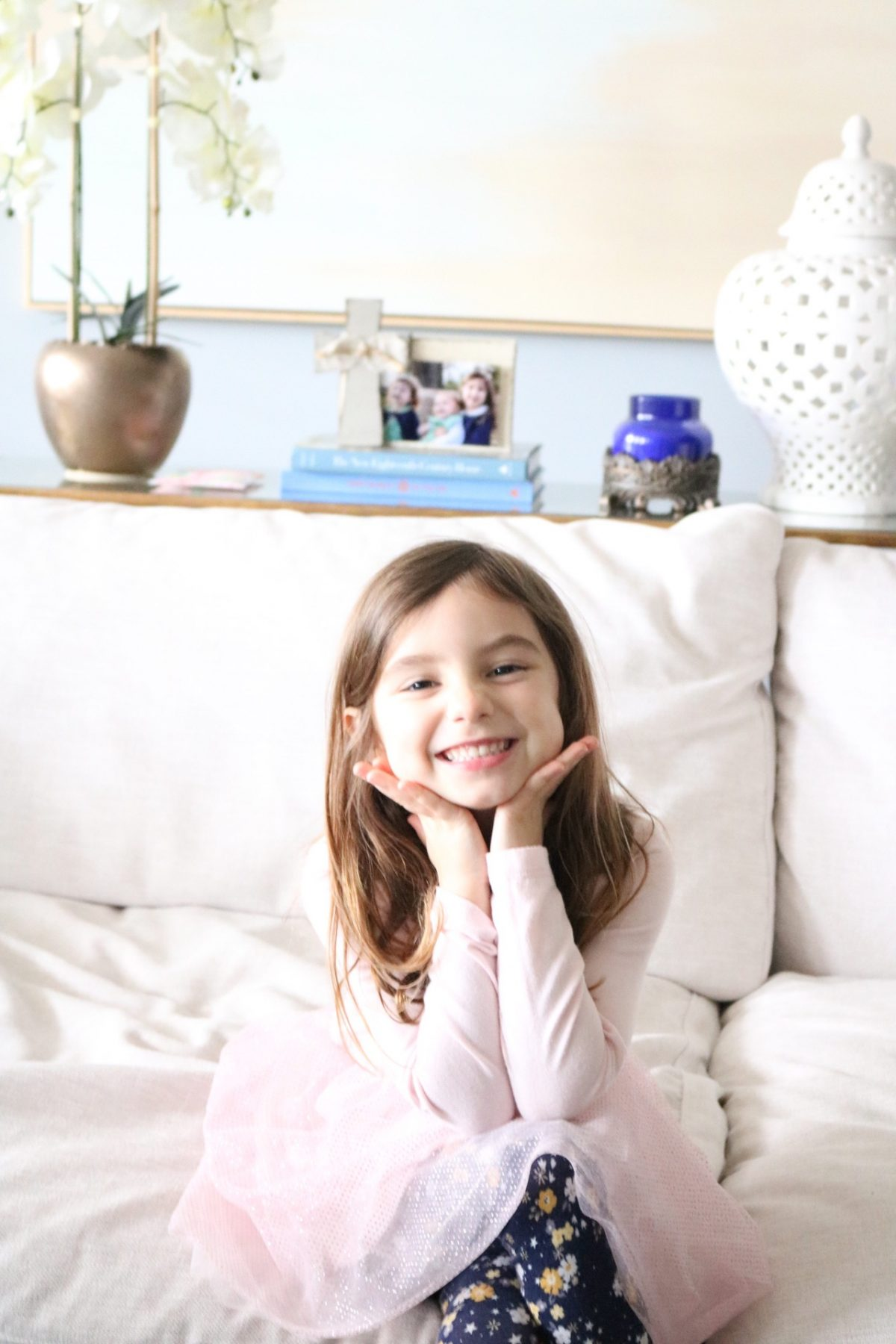 Little girl wearing pink sitting with hands under chin smiling on big white couch