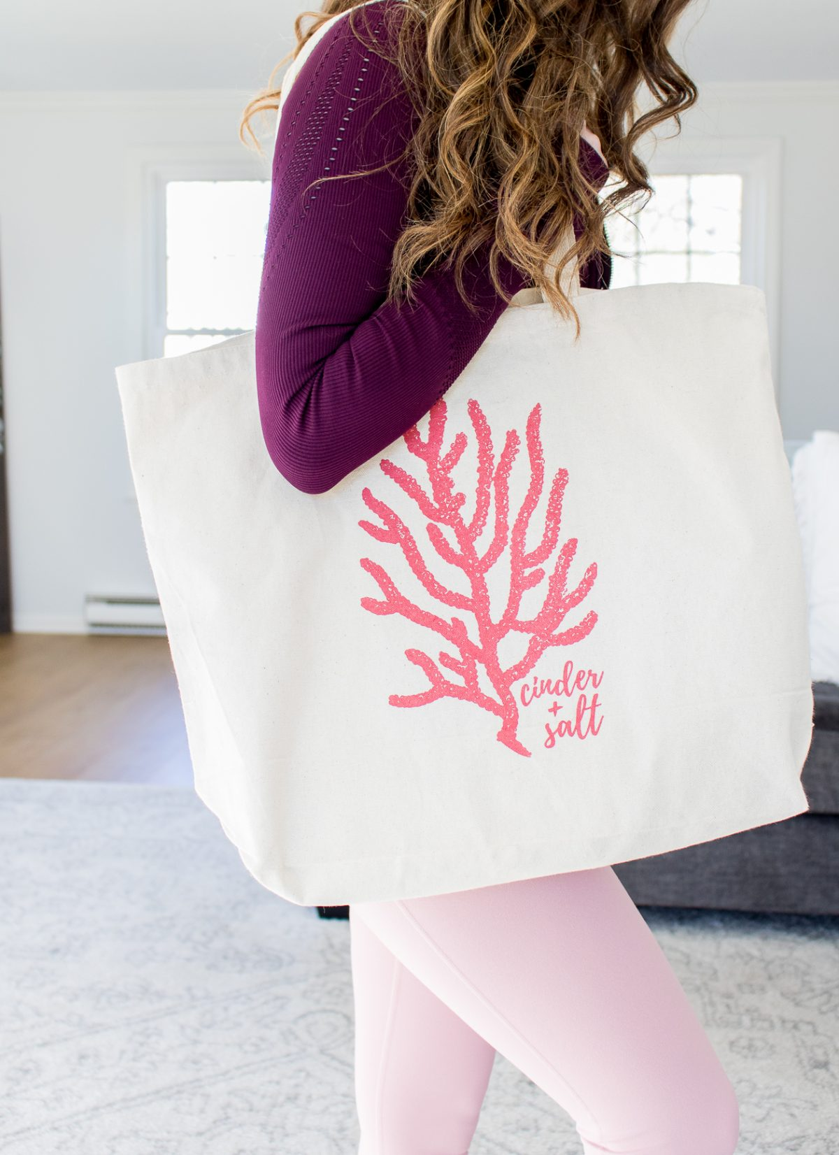 Woman holding a reusable tote from cinder + salt in middletown CT