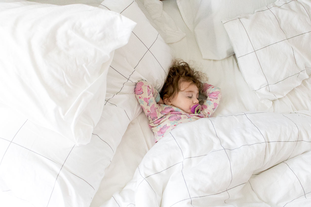 Little Girl wearing pink peppa pig pajamas with a paci in her mouth sleeping in a big white bed