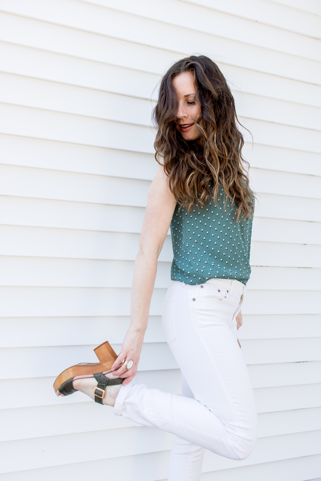 Woman holding platform sandal wearing white denim with green tank