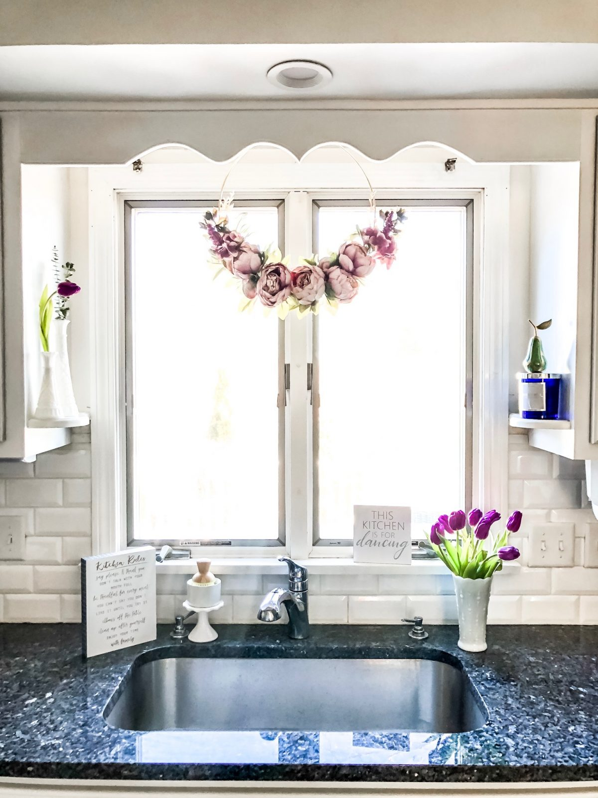 Purple floral ring wreath hanging over kitchen sink in window