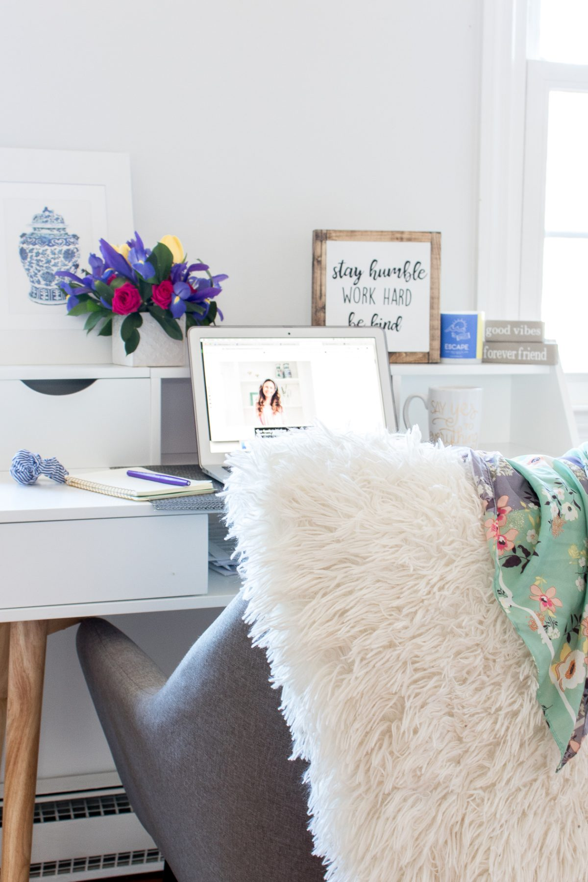 White desk with fresh flowers on the desk in background