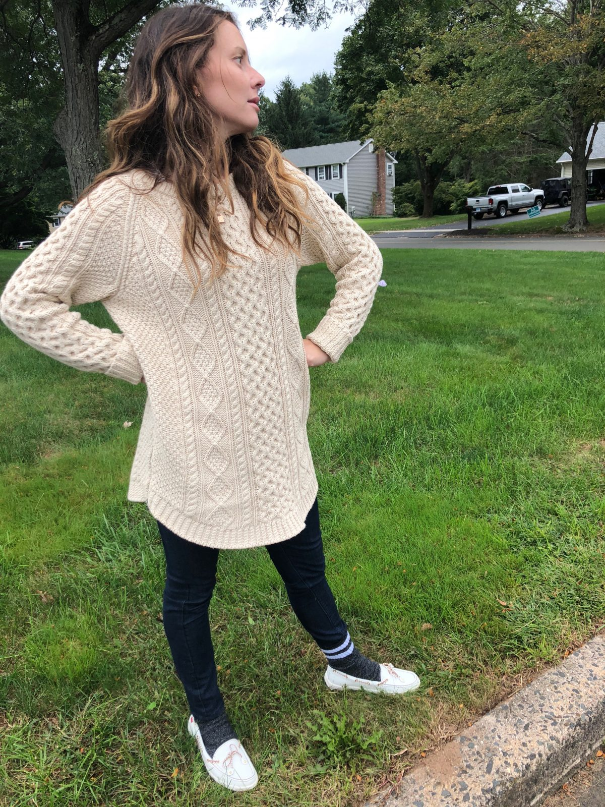 Woman wearing cable knit shirt with leggings socks and loafers on un-mowed lawn