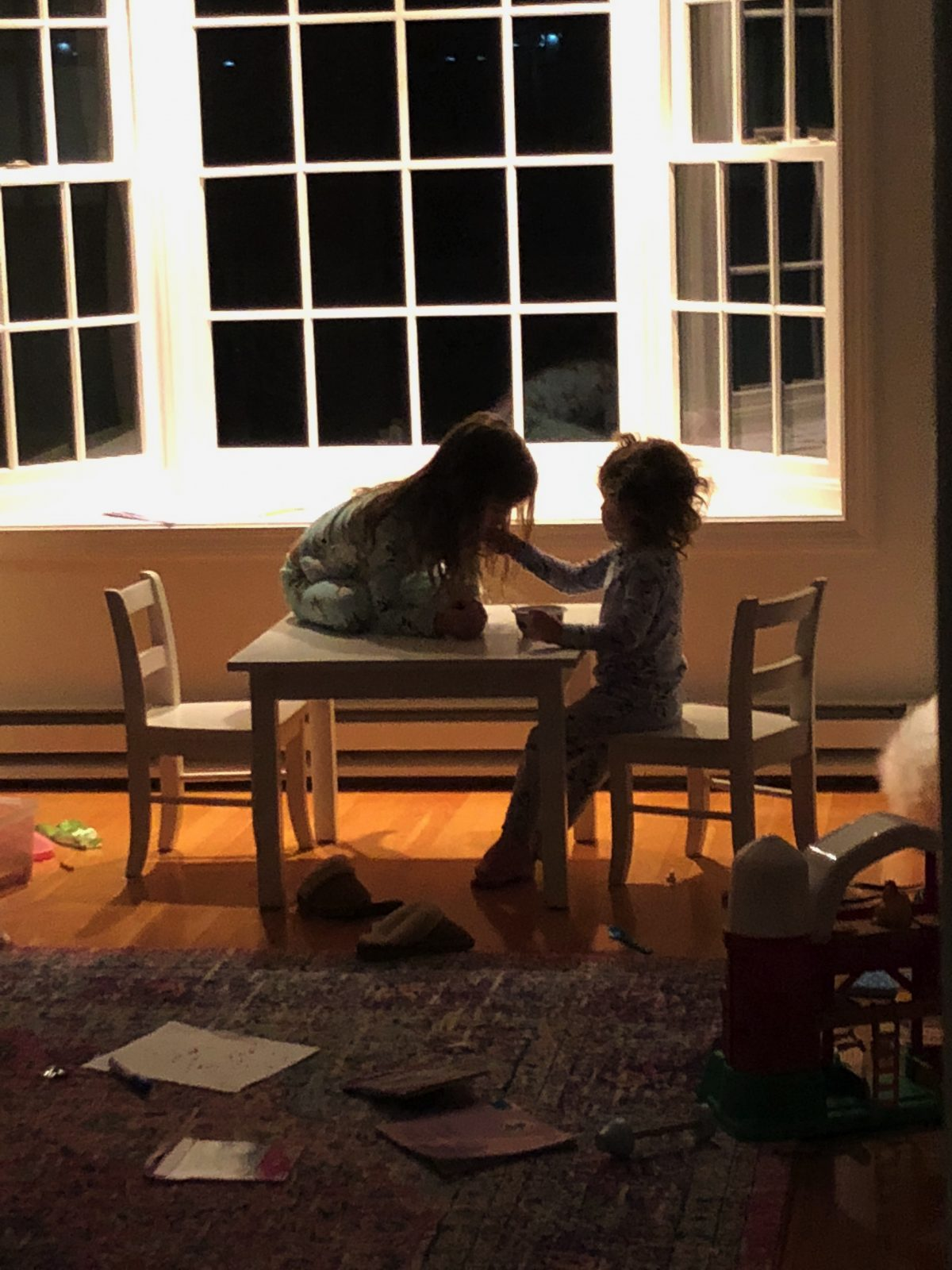 Dark photo of little girl sitting on top of table while sister feeds her food in a messy room
