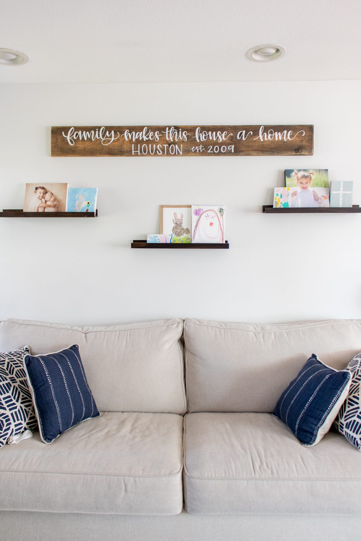 Living room couch with sign above that says Family Makes This House a Home and three floating shelves with children's photos and art work