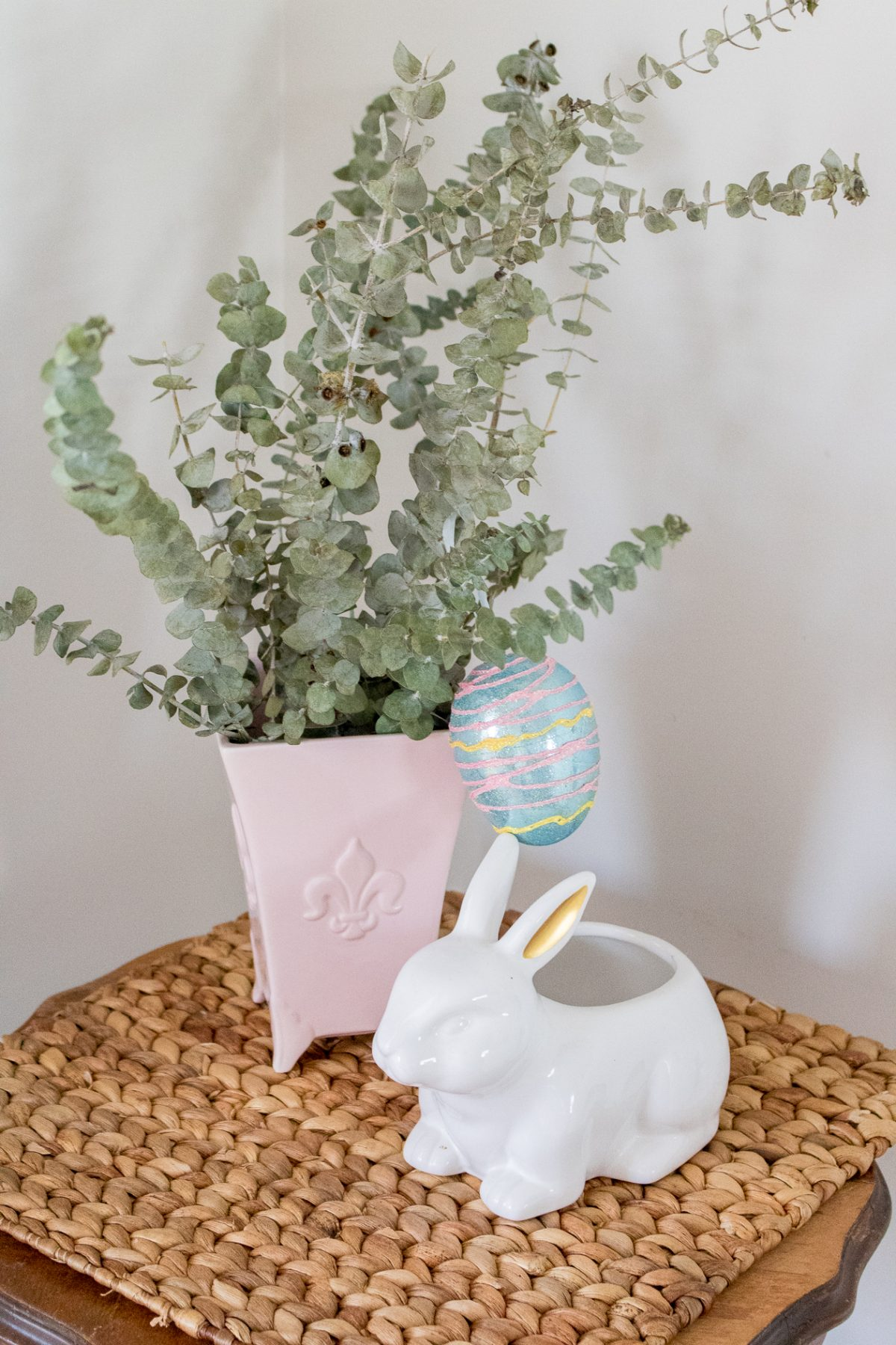Eucalyptus in pink vase with pastel egg hanging off the branch and a white bunny on a table
