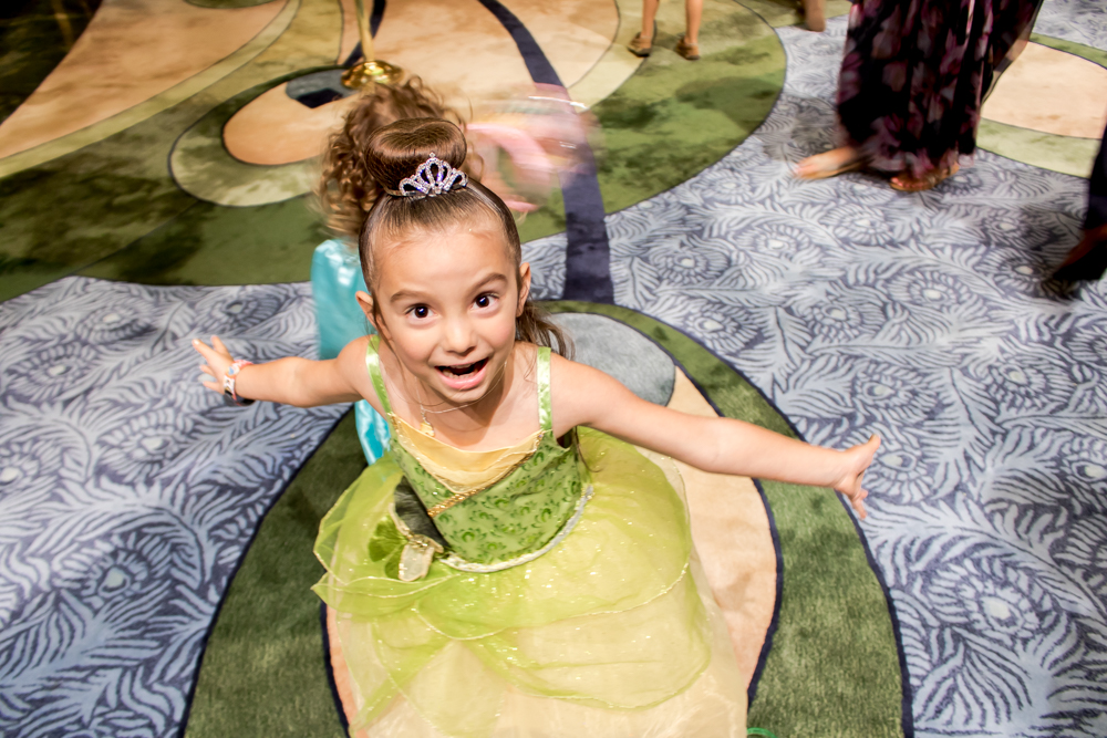 Little Girl in Princess Gown Smiling as She Spins around in Circles