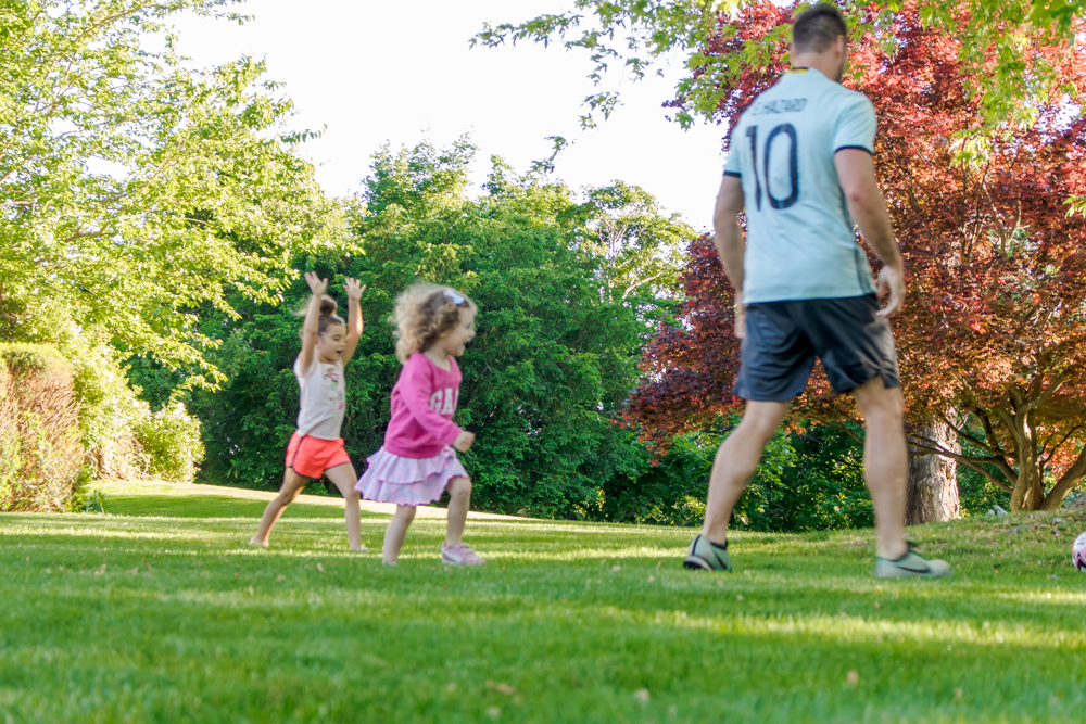 girls playing soccer in the front yard with dad