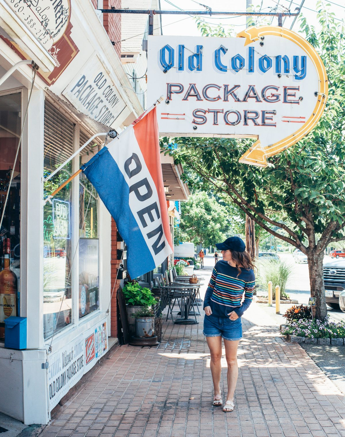 Woman in striped shirt and navy blue hat and denim shorts looking in Old Colony Package Store in Old Saybrook