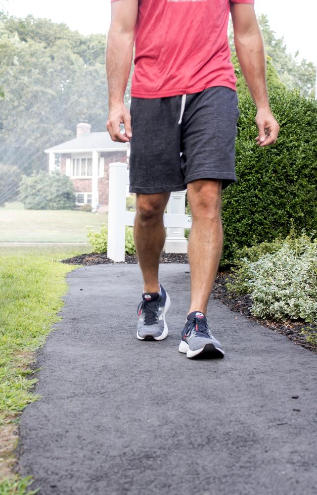 Man wearing red shirt and gray shorts and running shoes walking yard
