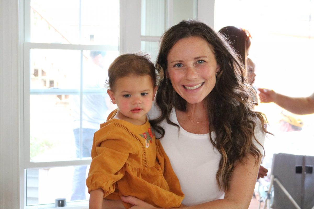 Woman in white shirt smiling and holding a little girl in a yellow dress