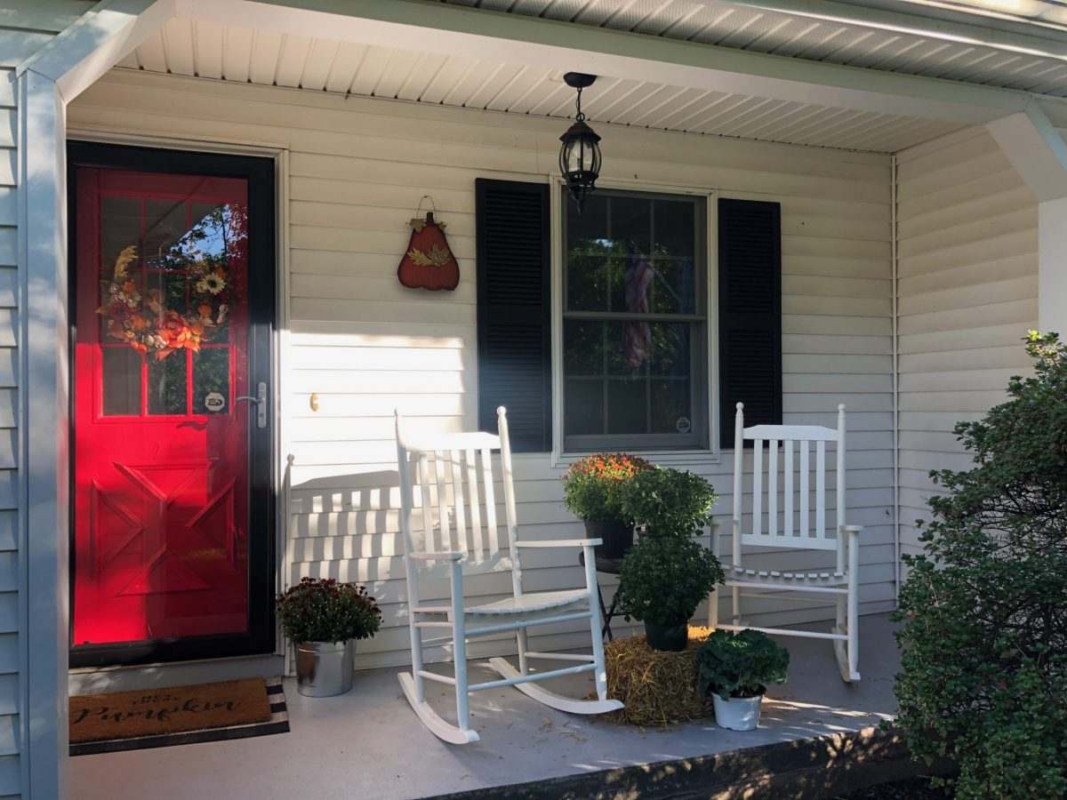 Fall Decor on White Colonial Home Breezeway with Red Door