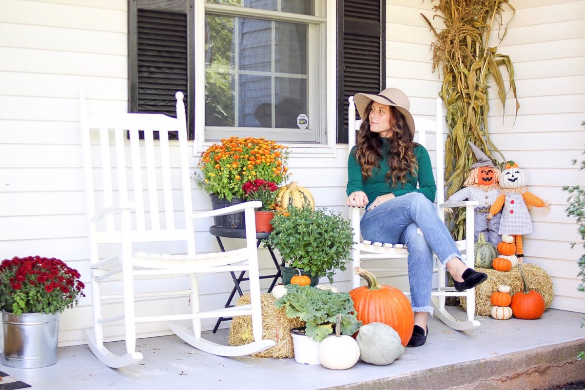 Front Porch Decorated for Fall and Woman In Rocking Chair