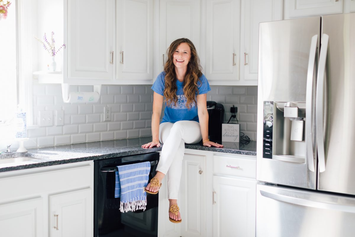 Smiling woman in blue shirt sitting on black countertop in white kitchen