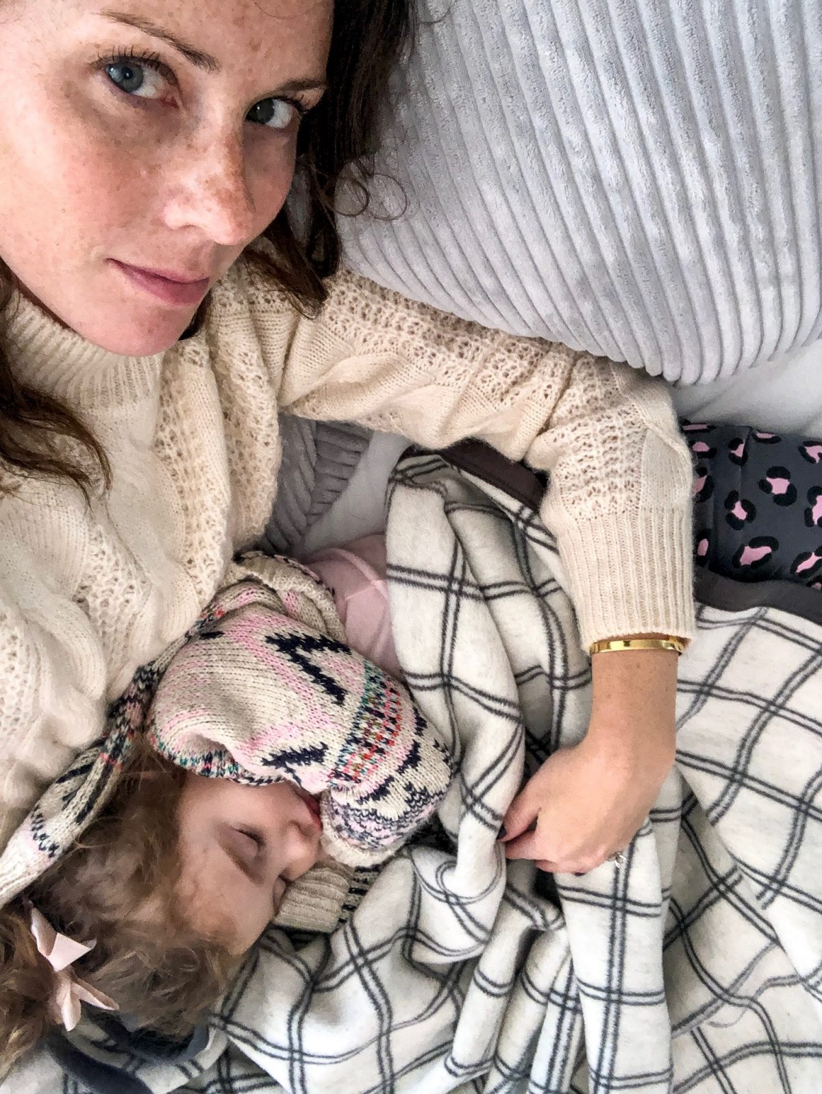 Mom wearing cable knit sweater with sleeping toddler in lap on Chappy Wrap Blanket