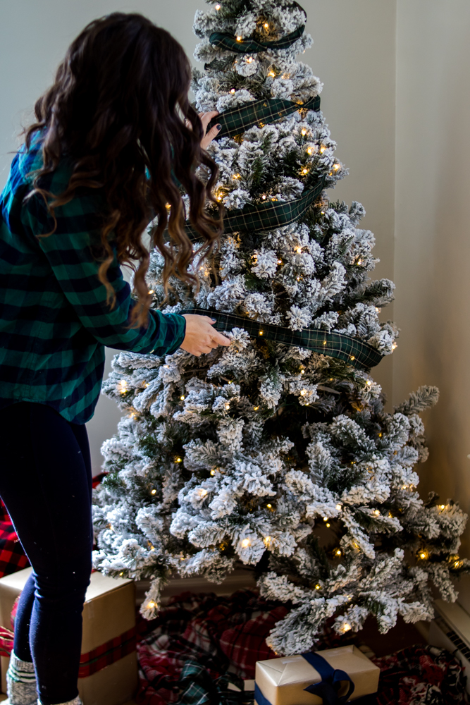 Woman in Plaid Shirt Putting Plaid Ribbon on Flocked Christmas Tree