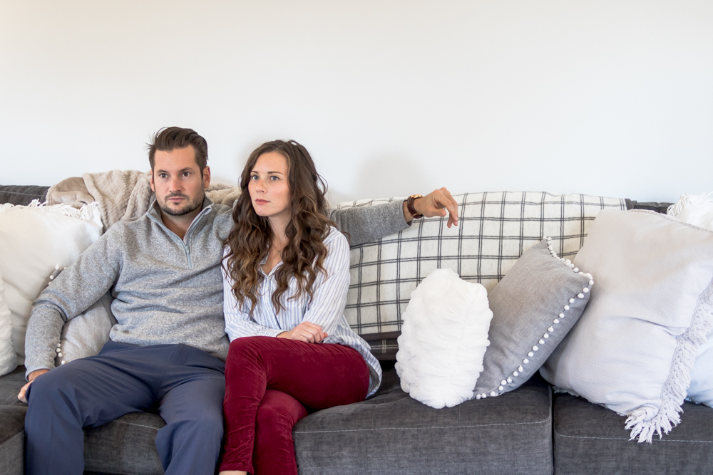 Husband and Wife sitting on couch not looking at each other
