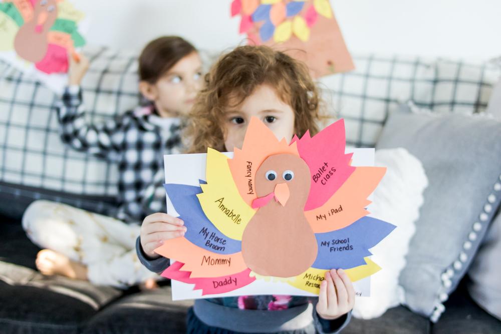 little girl holding a gratitude activity thankful turkey