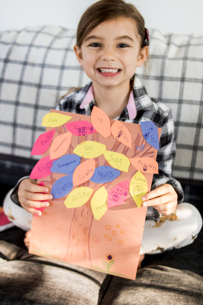Little girl wearing plaid holding a gratitude tree