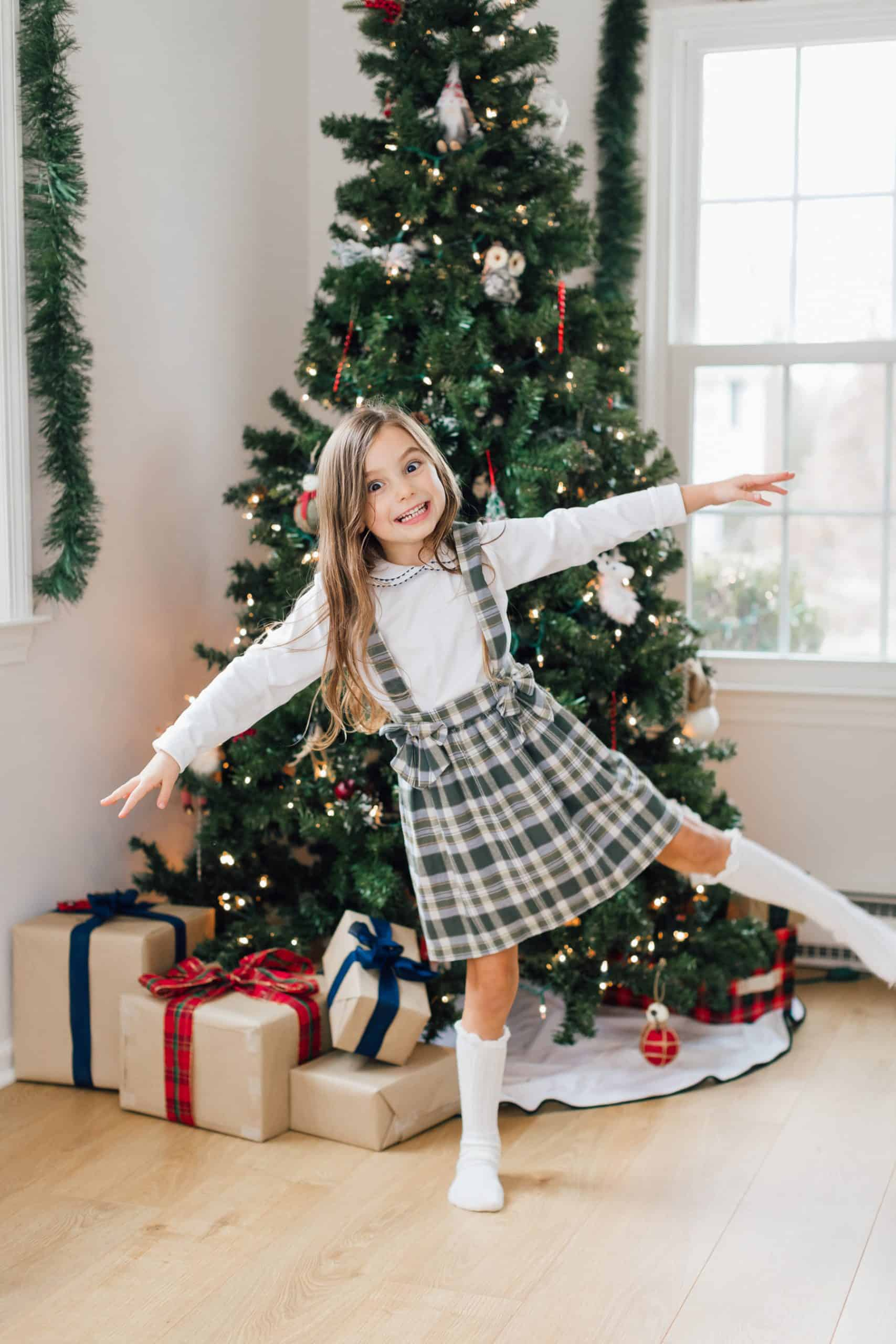 Little Girl in Front of Christmas Tree Being Silly