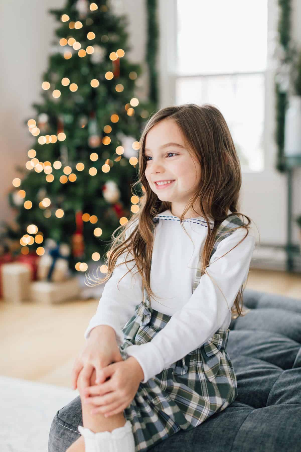 Little girl smiling in front of Christmas Tree