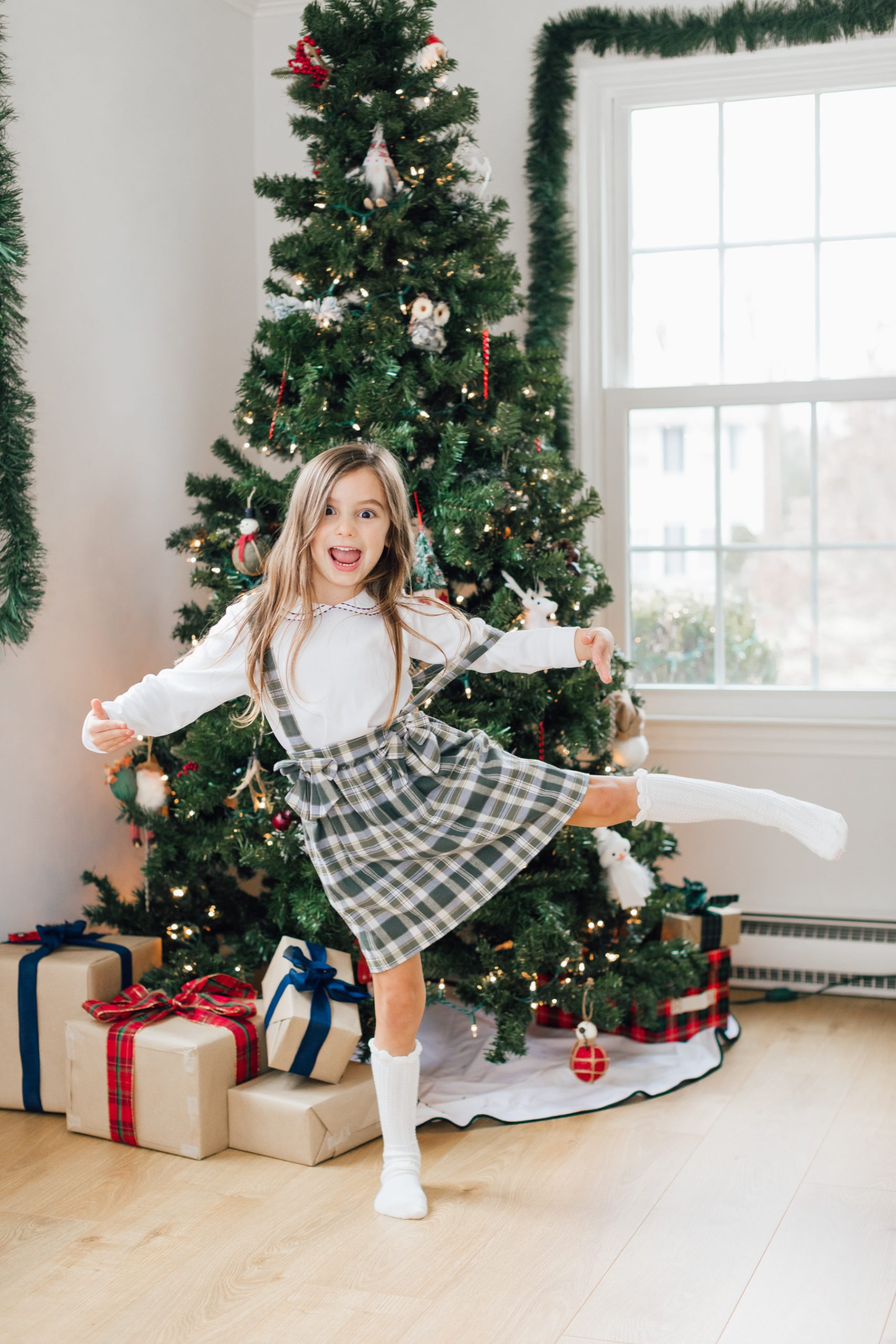little girl in green plaid jumper making a silly face and doing a dance move
