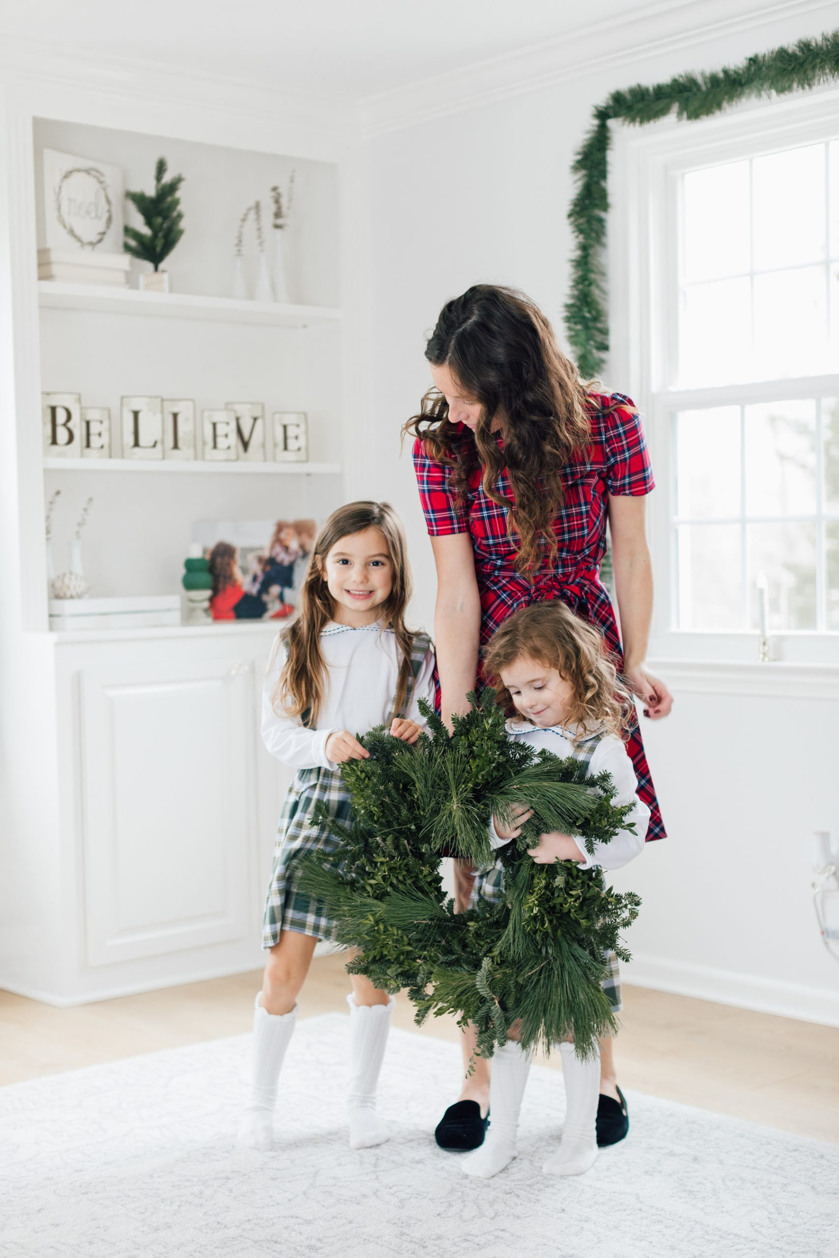 mom and daughters holding a green wreath