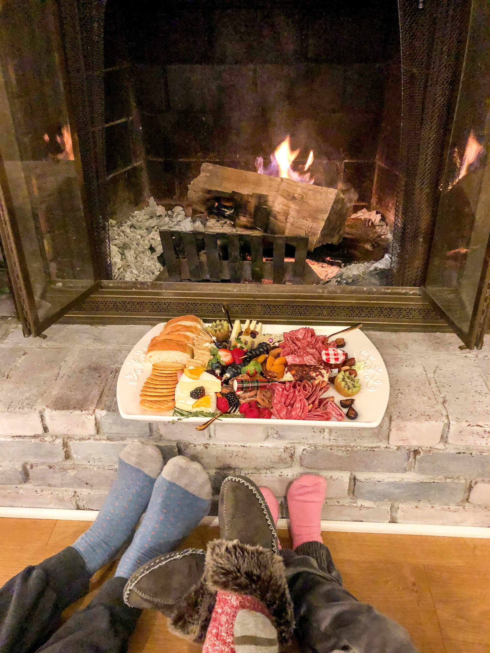 meat and greet charcuterie board in front of fireplcae