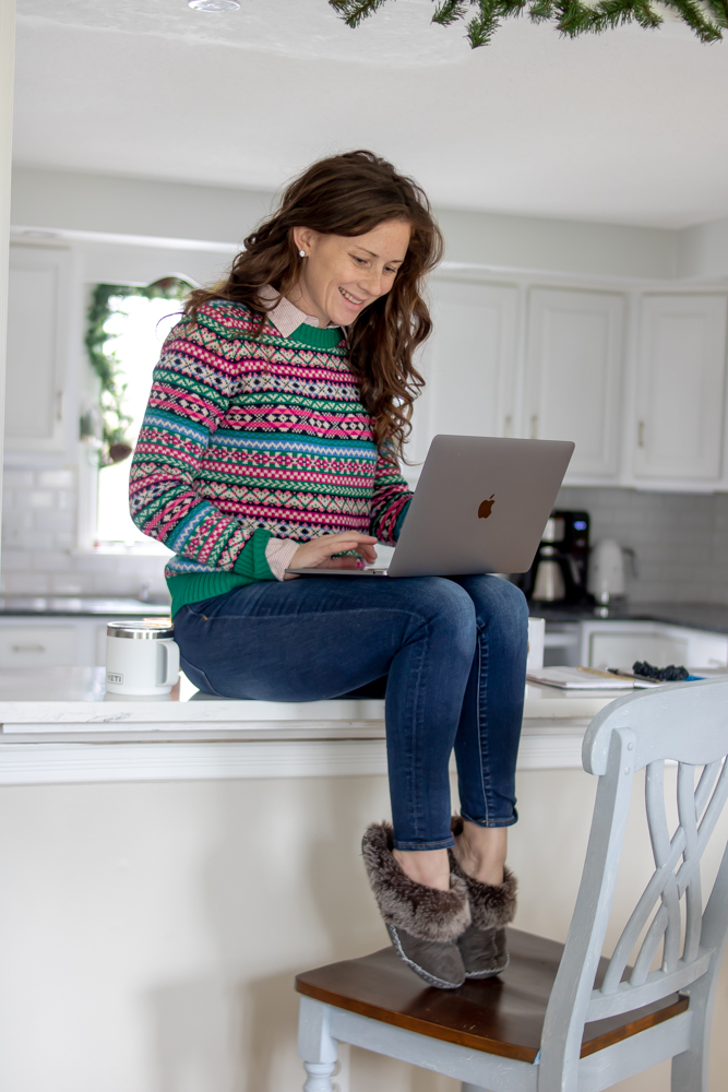 woman sitting on counter with laptop